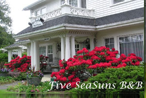 Shows the front of a Port Angeles, Washington Bed and Breakfast called Five SeaSuns with gorgeous blooming red rhododendrons surrounding the front step