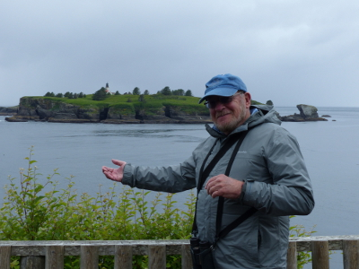 A birder stands on the Cape Flattery platform with Tatoosh Island and the lighthouse in the background