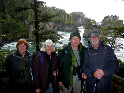 Four participants at Cape Flattery with the rocky Olympic Peninsula shoreline in the background