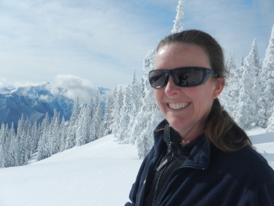 Olympic Peninsula tour operator Carolyn Wilcox smiling with snow covered trees and mountains in the background
