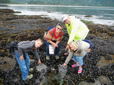 Two smiling grandparents and their grandkids are excited to point out what they have discovered in an Olympic Peninsula tidepool