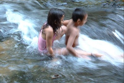 Two young children sliding down natural water slide in a stream