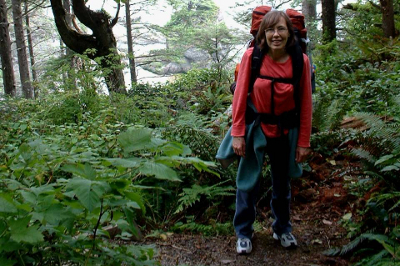 Backpacker surrounded by ferns on a headland trail on the Olympic Coast