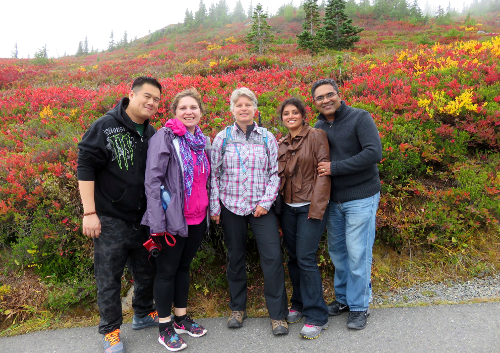 A guide stand in the center of a small group with colorful Mount Rainer shrubs in the background