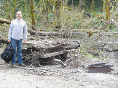 A man stands next to a picnic table covered in woody debris in the Elwha Campground