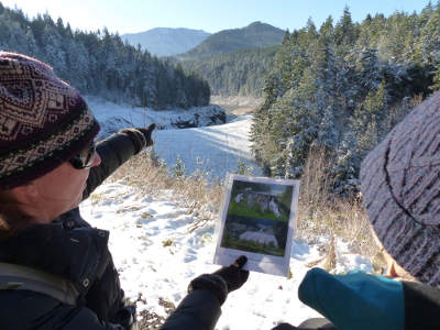 Olympic Peninsula tour operator Carolyn Wilcox points to the site of the former Elwha Dam and holds up historic photos taken from that site