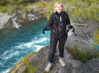 A woman stands smiling with the turquoise Elwha River pooling behind her before it enters Rica Canyon