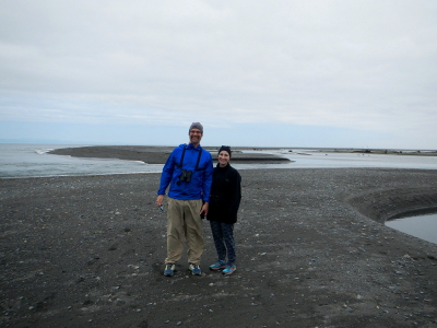 A couple stands on an expansive beach that has formed at the mouth of the Elwha River