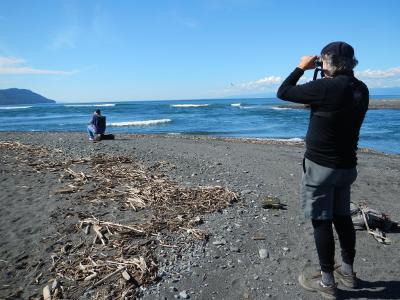 One participant looks though binoculars while another snaps a photo of the new sandy beach at the Elwha River Mouth