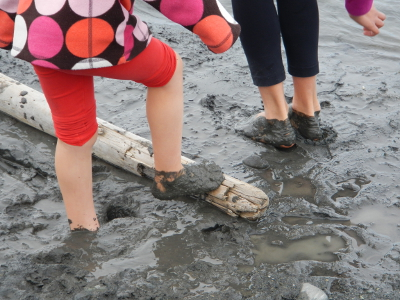 The feet of two young girls are immersed in dark grey Elwha River sediment that looks like clay