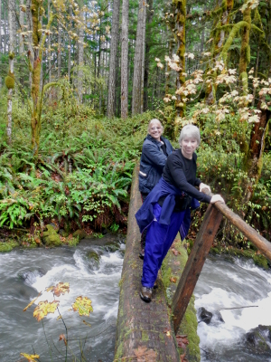 Two smiling hikers crossing a large Elwha River tributary on a narrow bridge with a railing on only one-side of the bridge