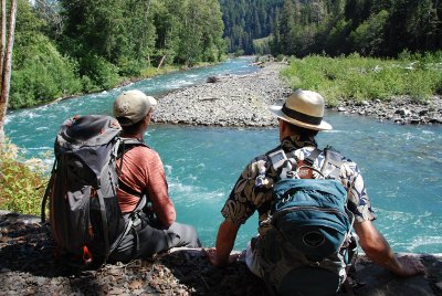 A participant and an Olympic National Park hiking guide sit enjoying a beautiful stretch of blue Elwha River