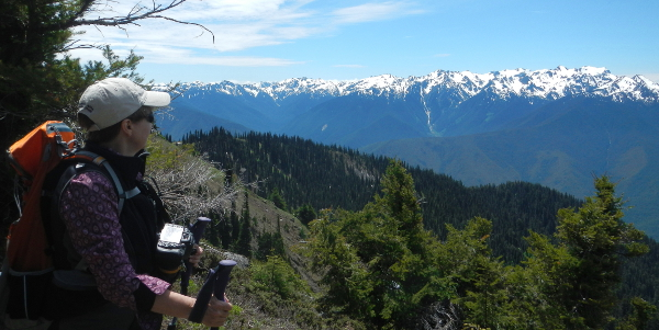 An Olympic Peninsula hiker has her large camera connected to her chest and takes a moment to pose for a photo while enjoying the majestic Olympic Mountains