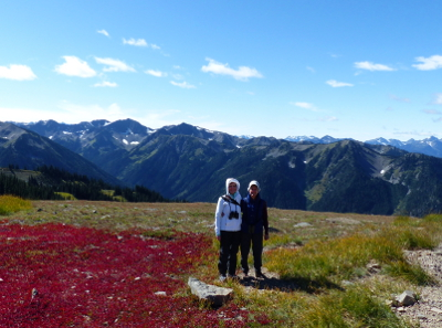 Two birders smiling on Obstruction Point Road at Hurricane Ridge with snow-capped mountains towering in the background