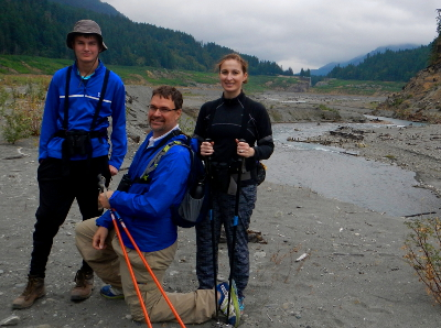 Three tour participants smile and pose in front of the Glines Canyon Gap in the former Mills reservoir lakebed on the Elwha River
