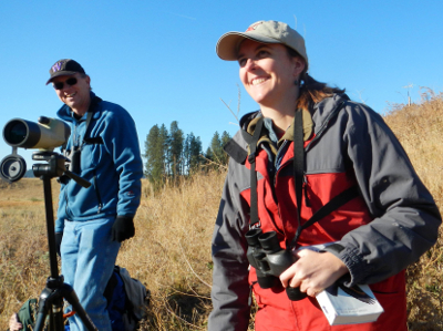 Olympic National Park birding guide and birding participant are smiling and taking a moment away from the spotting scope