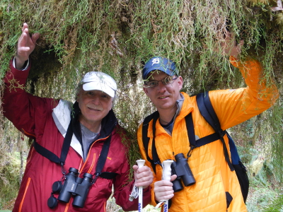 Two smiling multi-generational participants with binoculars part the strands of curtain moss in the Hoh Rainforest