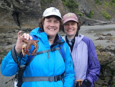 Two participants smile and one is holding either a dead crab or a crab carapace in Olympic National Park