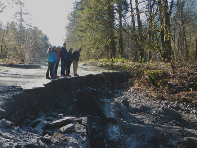 A family stands at the edge of a portion of destroyed roadway in Elwha River Valley