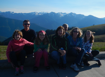 A family that includes three generations pose for a photo with a view from Hurricane Ridge