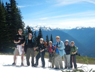 Seven hikers who are decked out in hiking gear pose on the snow at Hurricane Ridge with the mountains in the distance