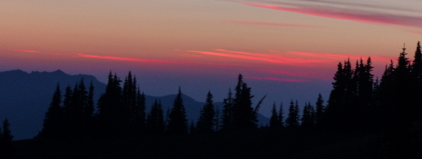 A dark line of trees against a backdrop of blue mountains with red streaks across the sky