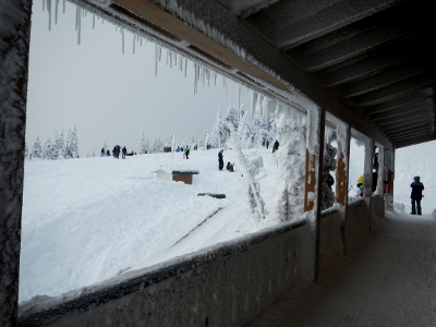 A view looking out towards people playing in the snow from the Hurricane Ridge Visitor Center porch bordered by icicles