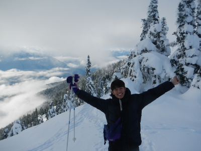 A jubilant participant on a Hurricane Ridge snowshoe tour puts his hangs up in the air on a particularly sunny day with snow-laden trees in the background
