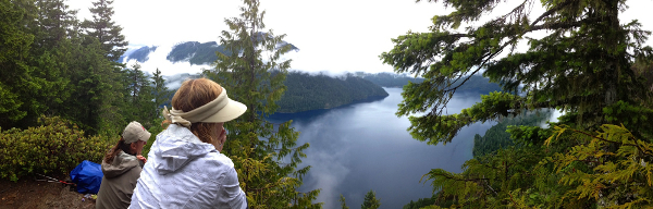 Two hikers sit to enjoy the stunning view of Lake Crescent from above, which is peeking out through the clouds