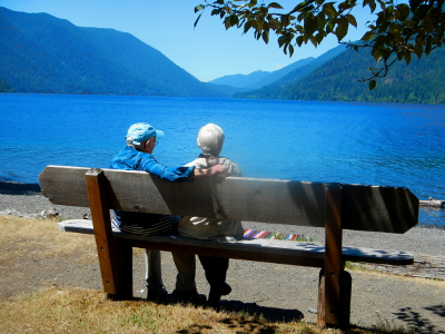 A couple sits on a bench enjoying the stunning view of Lake Crescent and surrounding coniferous forest scenery on a beautiful summer day