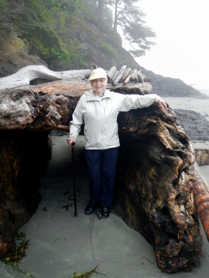 One participants stands smiling next to a huge piece of woody debris on the beach