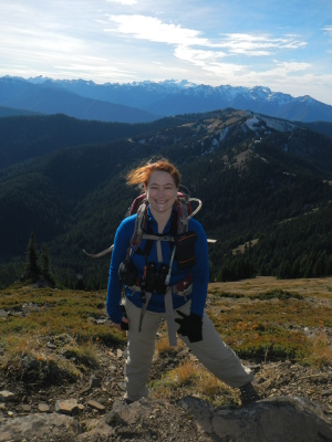 A woman with a backpack stands smiling with wisps of her red hair gleaming in the sun and Mount Olympus and other Olympic Mountains gleaming in the distance