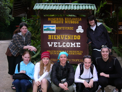 Naturalist and hiking guide Carolyn Wilcox with six students posing in front of a Monteverde Costa Rica Cloud Forest sign