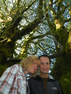 Looking up at a smiling couple with a huge mossy Bigleaf Maple in the background