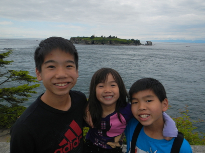 Three siblings stand shoulder to shoulder smiling at the end of the Cape Flattery trail with Tatoosh Island in the background