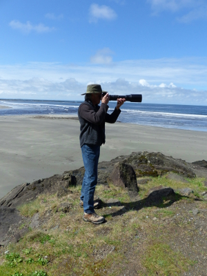 A photographer stands against Hobuck Beach in Neah Bay supporting a huge camera lens with both hands
