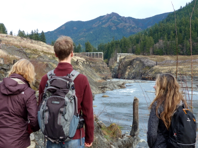 Three hikers look towards the Glines Canyon Dam Gap, which is the obvious tall space where the dam used to be located