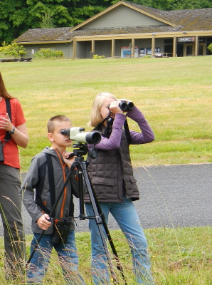 Two kids looking through a spotting scope and binoculars and standing in front of the Olympic National Park Visitor Center