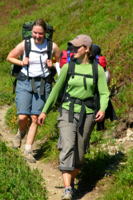 Two backpackers hiking on a narrow subalpine trail when visiting Olympic National Park