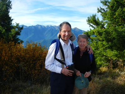 A couple stands smiling on Hurricane Hill with the Olympic Mountains and a brightly colored yellow shrub in the background