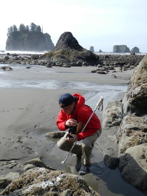 A man kneels down to investigate intertidal life during low tide with expansive beach, rocks, and islets in the background