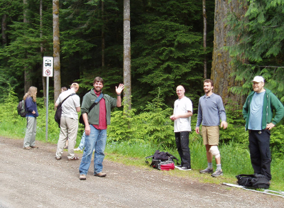 Seven Clallam Transit passengers waiting on the side of the road to take a trip through Olympic National Park