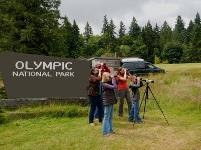 Five people looking through binoculars with a sign reading:  Olympic National Park