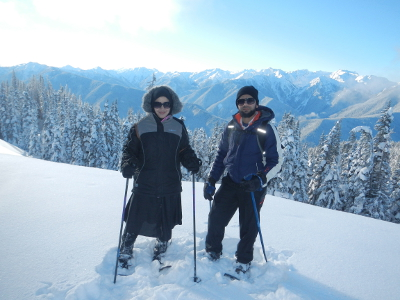 A couple in full winter on an Olympic National Park snowshoe tour pose with the Olympic mountains in the background