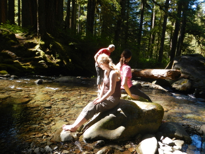 Two girls sit barefooted on a boulder in a Sol Duc stream watching their father wade in the stream