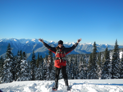 Olympic National Park tour guide Carolyn Wilcox stands in snowshoes against the Olympic Mountains with her hands raised above her head in joy