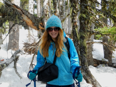 A smiling girl with oversized sunglasses wearing a blue coat, hat, and gloves snowshoes on her Olympic National Park vacation through a subalpine forest at Hurricane Ridge
