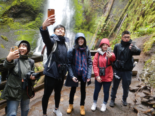 Five friends line up and take selfies with Marymere Falls and mossy and fern covered rock in the background