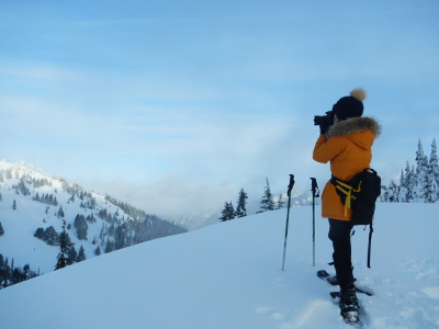 A woman on snowshoes taking a photograph of the winter wonderland at Olympic National Park's Hurricane Ridge