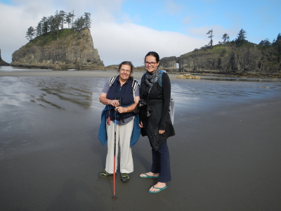 Two hikers stand on the beach smiling at low tide with an expansive sandy beach, small rocky island, and headlands in the background